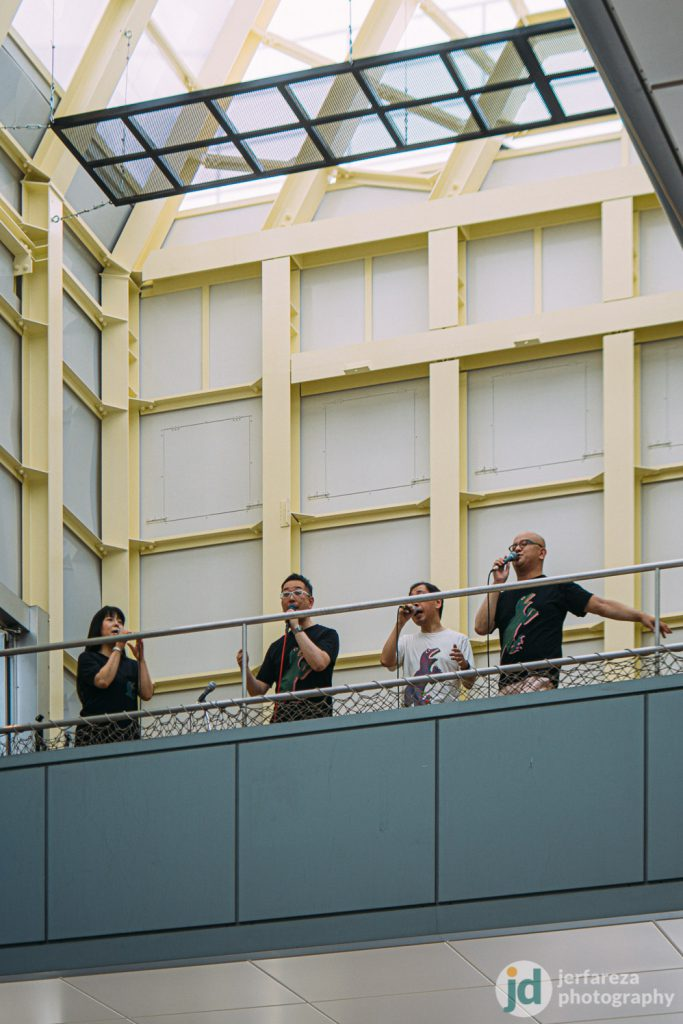 A group of singers performing on top of shopping arcade.