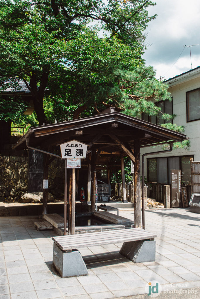 A foot-spa (ashiyu) in front of a small shrine.